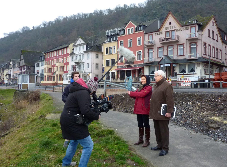 Filmteam, Künsterlin und Bürgermeister am Rheinufer von Sankt Goar
