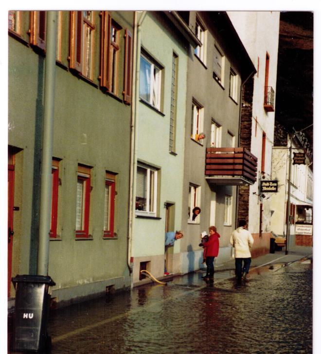 Überflutete Straße, Passanten in Gummistiefeln, Anwohnerinnen schauen aus den Fenstern